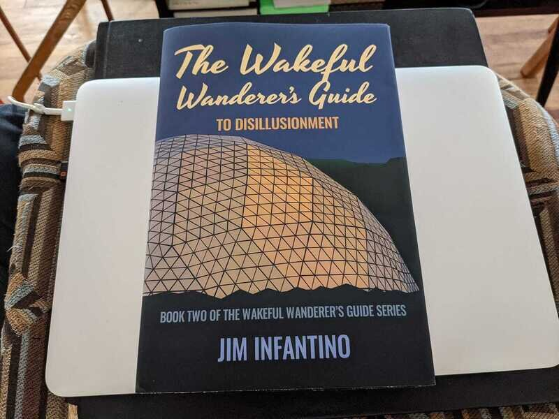hardbound copy of the wakeful wanderers guide to disillusionment on top of a laptop